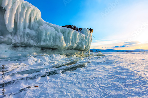 Staande foto Schip Old rusty ship on ice covered sunset standing on the shore