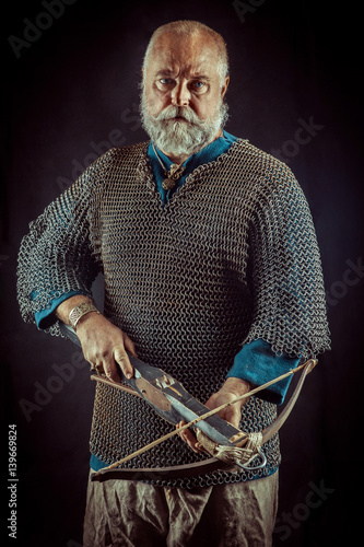 Poster Templar Knight posing with crossbow. Dark background.