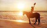 Brunette lady riding a horse alongside the coastline