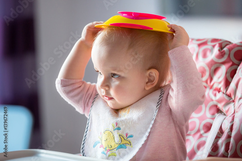 Little girl fussy eater sitting on the high chair