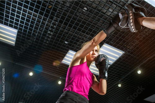 Póster Young adult woman doing boxing training with her coach