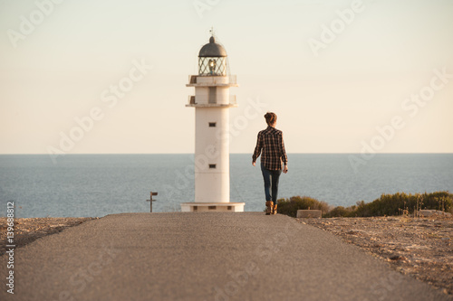 woman walking by a lighthouse
