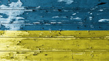 Ukraine flag on wood texture background with old paint peels