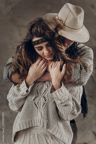 Poster Strong cowboy man in white stylish hat hugging beautiful brunette hipster girl f