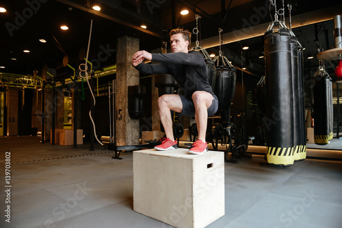 Póster Athletic man jumping on box
