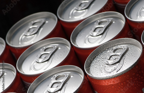 a group of red tin cans with water droplets closeup on a black background Poster