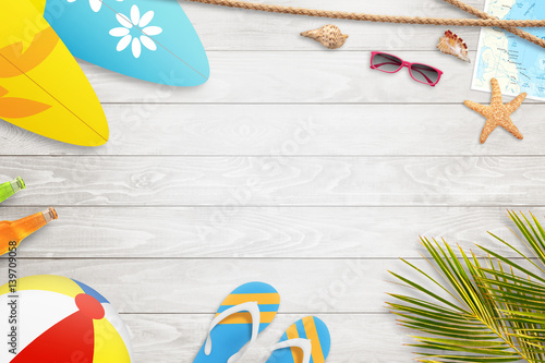 Summer holiday background with free space for text. Slipers, palm, ball, surfboard, sunglasses, map, starfish and shell beside. White wooden table. Top view.
