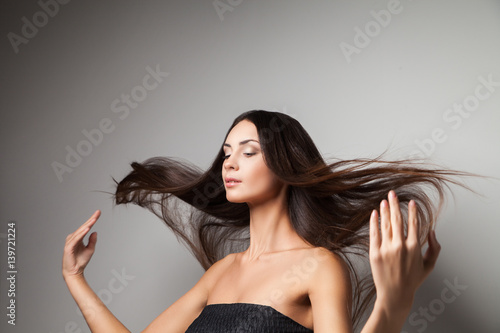 Poster Young woman touching up her straight hair with hands