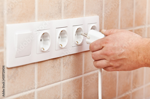 Male hand plugging power cord into electrical socket in the wall Poster