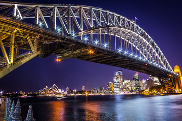Sydney harbour bridge at sunset with bright illumination of steel arch and columns reflecting in the blurred waters of harbour with Sydney city CBD in the background