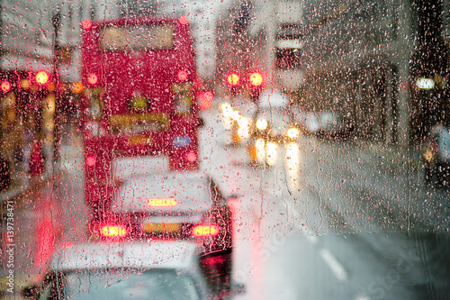 Rain in London view to red bus through rain-specked window Poster