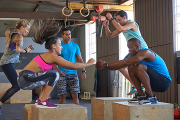 Trainer motivating class doing box jumps fitness boot camp training