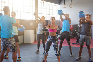 Group kettle bell class in bright sunlit gym