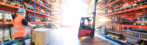 Sticker Logistik im Warenlager - Arbeiter mit Hubwagen und Gabelstapler am Hochregal // Logistics in warehouse - Worker with pallet truck and forklift truck on high rack