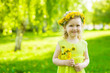 Little girl with dandelions in summer park