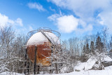 Old rusty spherical gas tank in forest