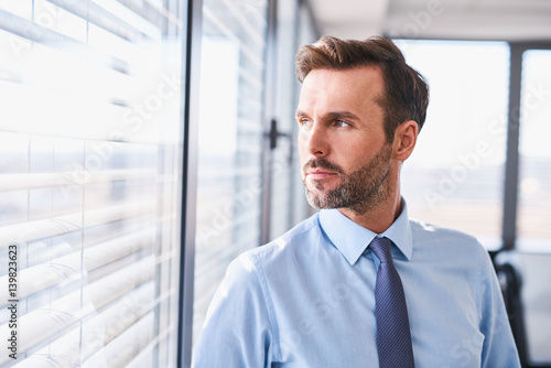 Fridge magnet Portrait of handsome businessman standing at office looking out the window