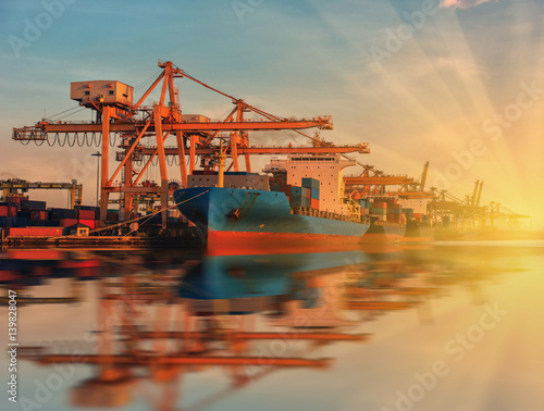 container ship in import export and business logistic.By crane , Trade Port , Shipping.Tugboat assisting cargo to harbor.