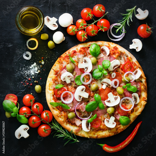 Food ingredients and spices for cooking mushrooms, tomatoes, cheese, onion, oil, pepper, salt, basil, olive and delicious italian pizza on black concrete background. Copyspace. Top view.