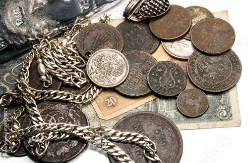 Srebro w sztabach, antyczne srebro i brąz monety i biżuteria leżące na starych banknotach. Na białym tle.