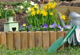 accessoires de jardin devant bordure en bois fleurie - 139833270