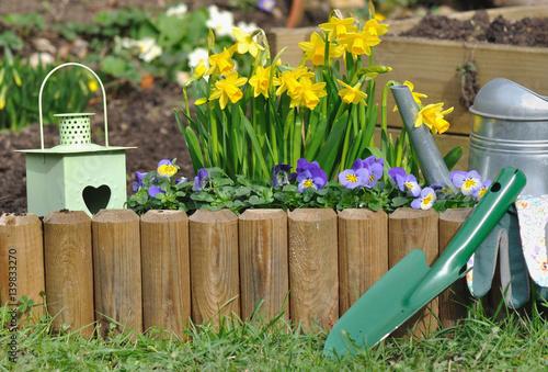 accessoires de jardin devant bordure en bois fleurie