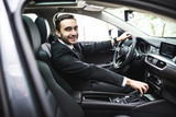 transport, business trip, destination and people concept - close up of young man in suit driving car look at camera - 139834022