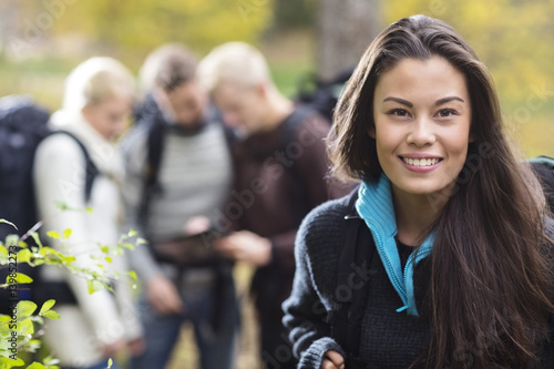 Beautiful Female Hiker With Friends Discussing In Background