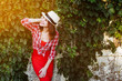 Quadro young girl in a red dress and hat smiling and enjoying life. Health. Lifestyle. Sunny