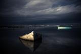 deux barques sur un étang , avec des tonalités sombres et contrastées
