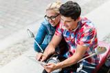 Junges Paar auf Städtereise in Berlin plant Tour mit Vespa auf einem Tablet PC