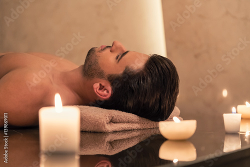 Man relaxing on massage table at Asian spa and wellness center