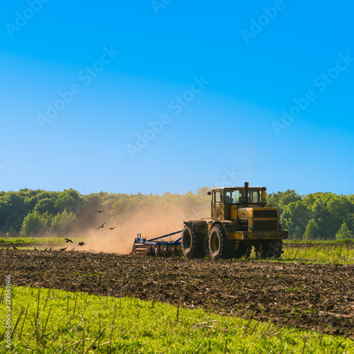 Poster Tractor cultivating field at spring. Russian agriculture