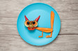 Amazed cat made of carrot and cucumber on plate and table