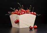 Ripe cherry in wooden box isolated on black background