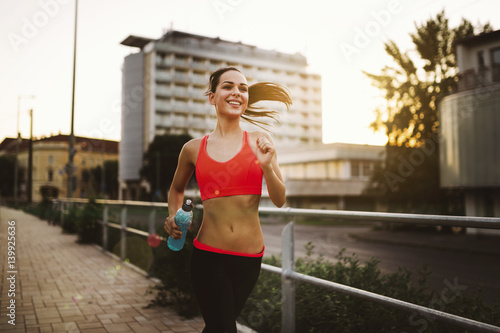 Beautiful female jogger doing her run in sunset