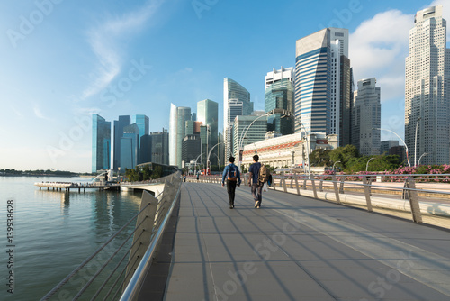 Pedestrians walk along bridge near Marina bay in Singapore with Singapore skyscraper and Merlion park in background Poster