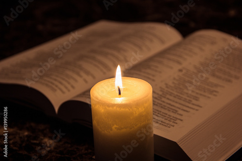 Obraz Fotograficzny Candle & the bible in the dark