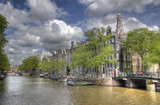 Canal with trees and historical buildings in Amsterdam