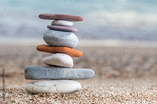 Foto op Canvas Stenen in het Zand Pile of stacked stones on the sandy beach at Adriatic sea