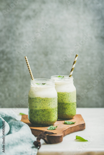 Ombre layered green smoothies with mint in glass jars with straws on wooden board, grey concrete wall background, copy space, selective focus. Clean eating, vegan, weight loss, healthy food concept