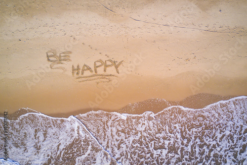 Be Happy written on the beach