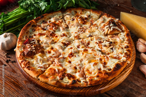 Papiers peints Pizzeria Fresh and yummy italian pizza cut into slices on rustic wooden table. Restaurant menu photo.