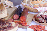 red sliced sausage on wooden board