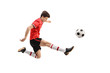 Teenage soccer player kicking a football
