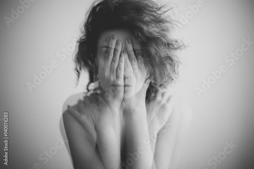 Double exposure black and white portrait of a woman covering her face and eyes with her hands