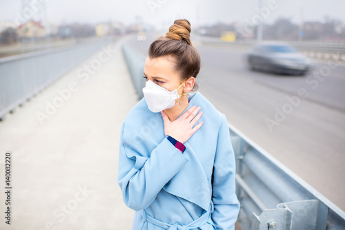 Young woman in protective mask feeling bad on the street in the city with air pollution