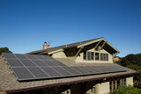 solar panels on roof of house. horizontal orientation, blue sky, gray panels on brown roof. - 140134236