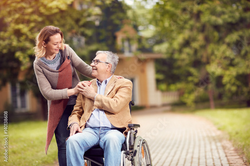 senior man in wheelchair with caregiver daughter.