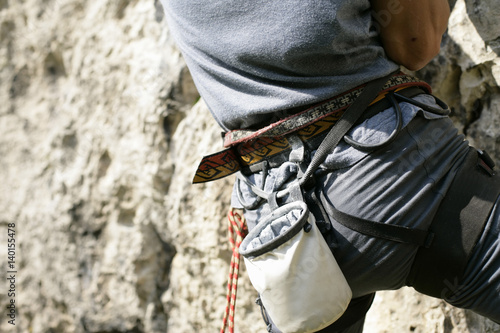 Poster Young man with a harness and a chalk bag is climbing up a rocky wall (part of),